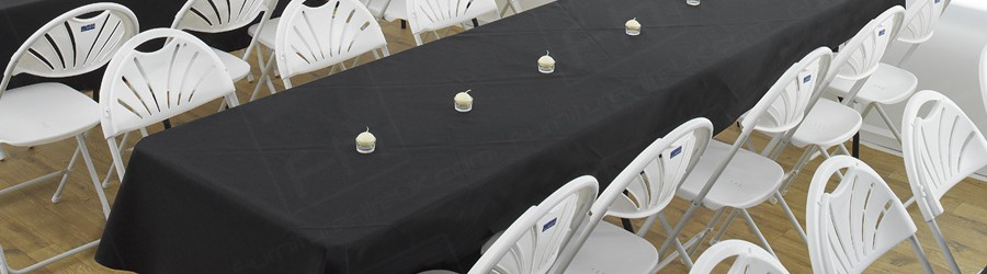 covered trestle tables and white folding chairs